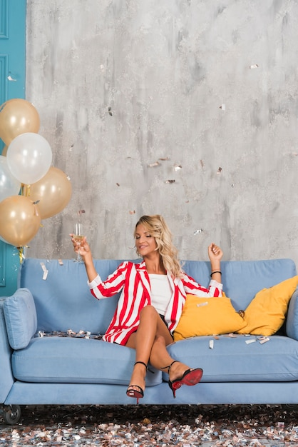 Frau, die auf sofa mit champagner sitzt Kostenlose Fotos