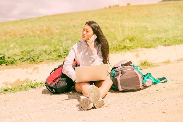 Frau, die auf straße sitzt und am handy unter rucksäcken spricht Kostenlose Fotos