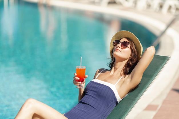 Frau, die auf sunbed holdinggetränk legt Kostenlose Fotos