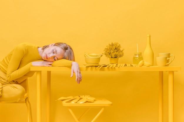 Frau, die auf tabelle in einer gelben szene schläft Kostenlose Fotos