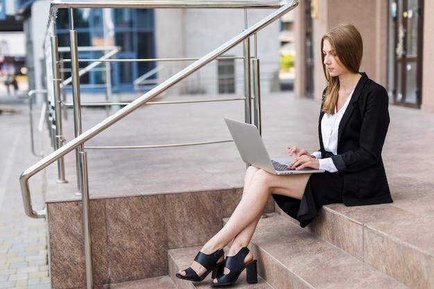 Frau, die auf treppen unter verwendung ihres laptops sitzt Kostenlose Fotos