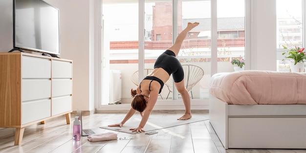 Frau, die auf yogamatte ausübt Kostenlose Fotos