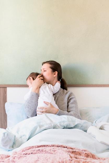 Frau, die baby in den armen im bett küsst Kostenlose Fotos
