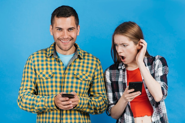 Frau, die beim betrachten des telefons ihres freundes entsetzt schaut Kostenlose Fotos