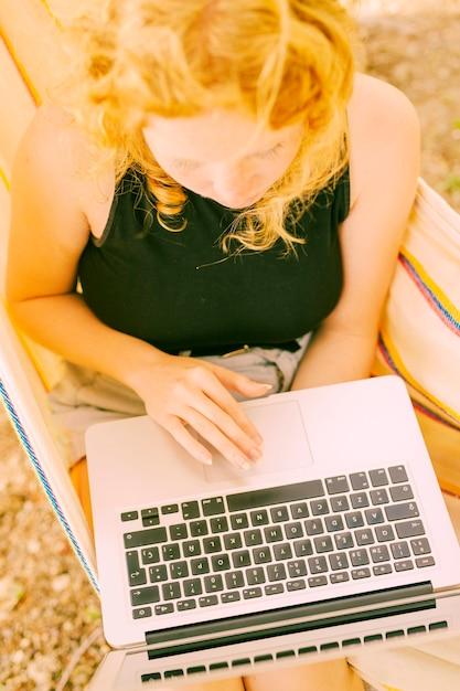 Frau, die berührungsfläche auf laptop verwendet Kostenlose Fotos