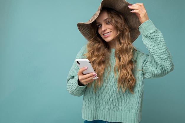 Frau, die blauen pullover und hut trägt, die lokal über blauem hintergrund stehen, der im internet surft Premium Fotos