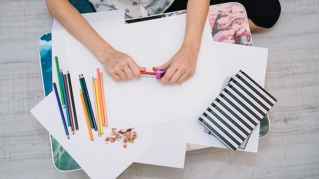 Frau, die bleistift bei tisch mit papieren und satz bleistiften schärft Kostenlose Fotos