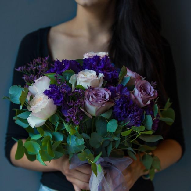Frau, die blumenstrauß der purpurroten, weißen rosen hält Kostenlose Fotos