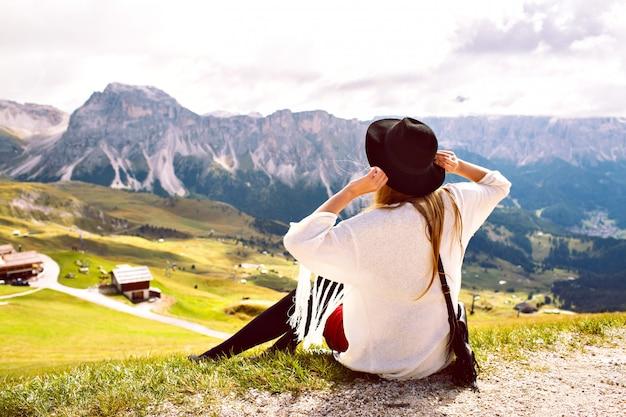 Frau, die boho stilvolles outfit trägt, allein geht und atemberaubende aussicht auf österreichische alpenberge genießt Kostenlose Fotos