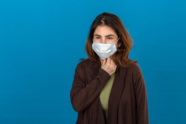Frau, die braune strickjacke in der medizinischen schutzmaske trägt, die krankes berühren des halses sieht, der unter schmerzen leidet, die über isolierter blauer wand stehen Kostenlose Fotos