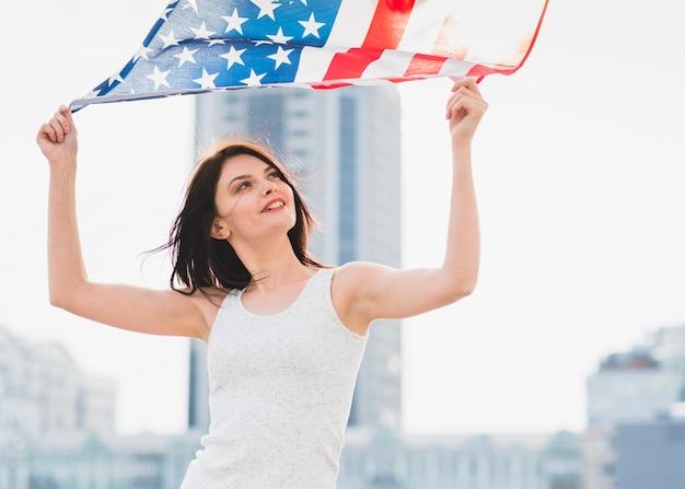 Frau, die breite amerikanische flagge auf hintergrund des geschäftszentrums wellenartig bewegt Kostenlose Fotos
