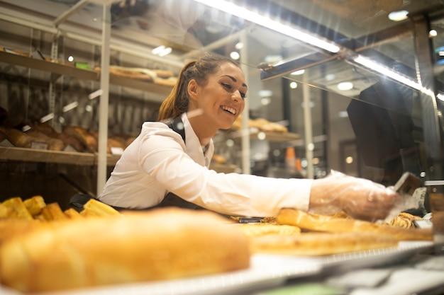 Frau, die brot für verkauf in der supermarktbäckereiabteilung vorbereitet Kostenlose Fotos