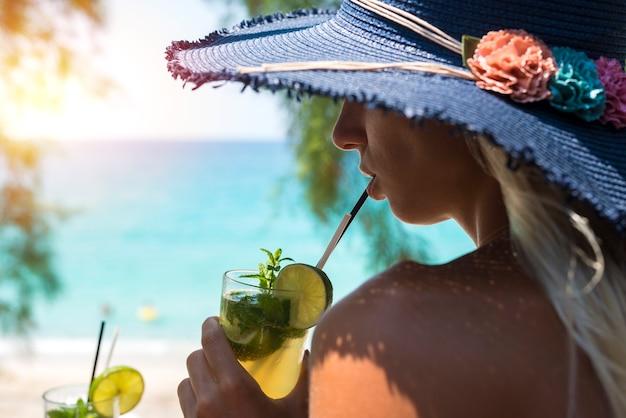 Frau, die cocktail in der strandbar trinkt Kostenlose Fotos
