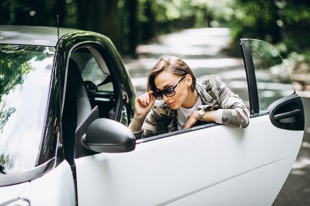 Frau, die das auto im park bereitsteht Kostenlose Fotos