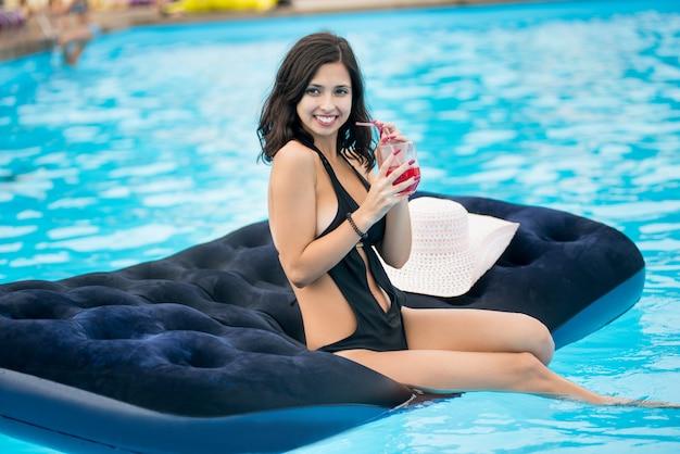 Frau, die das cocktail sitzt auf matratze im swimmingpool hält Premium Fotos