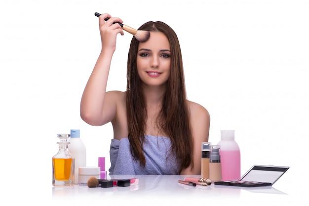 Frau, die das make-up lokalisiert auf weiß tut Premium Fotos