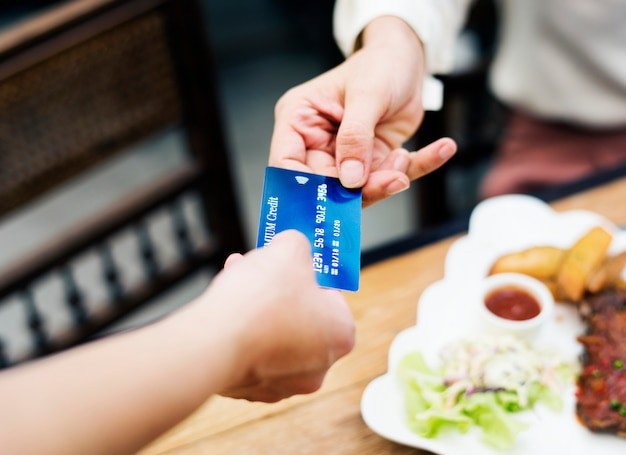 Frau, die das mittagessen mit kreditkarte am restaurant zahlt Kostenlose Fotos