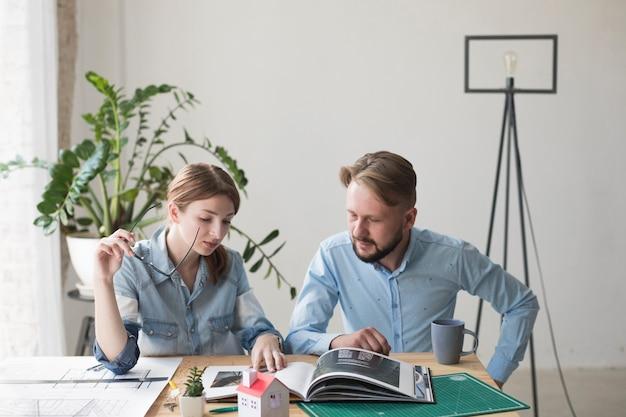 Frau, die das schauspiel betrachtet innenkatalog mit ihrem männlichen mitarbeiter im büro hält Kostenlose Fotos