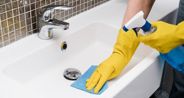 Frau, die das waschbecken reinigt Kostenlose Fotos