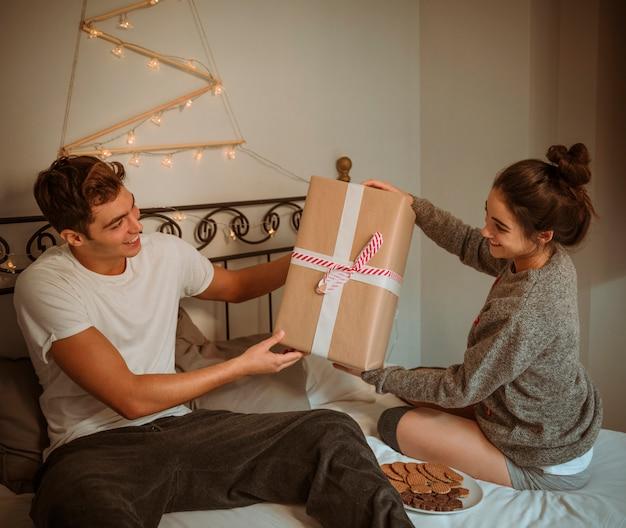 Frau, die dem mann geschenkbox gibt Kostenlose Fotos