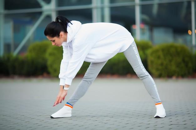 Frau, die den körper, übungen auf straße tuend ausdehnt Premium Fotos
