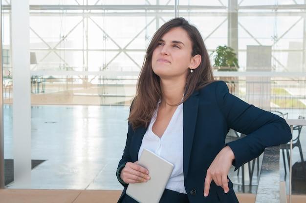 Frau, die den kopf anhebt, denkt und in der hand tablette hält Kostenlose Fotos