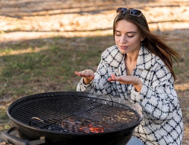 Frau, die die hitze des grills im freien testet Premium Fotos