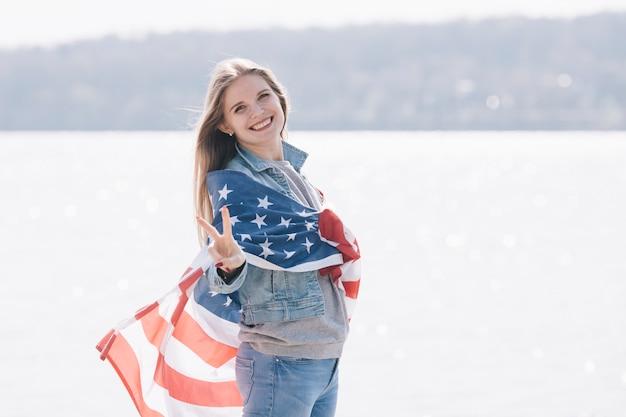 Frau, die die kamera eingewickelt in der amerikanischen flagge lächelt und betrachtet Kostenlose Fotos