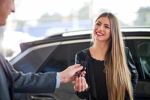 Frau, die die schlüssel für ihr auto in einem ausstellungsraum nimmt Premium Fotos