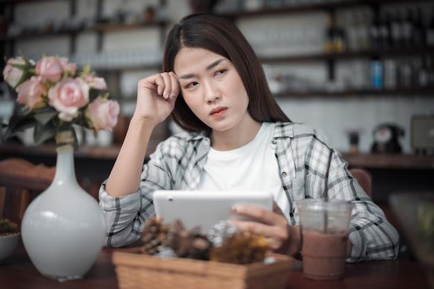 Frau, die digitale tablette verwendet und im café denkt Premium Fotos