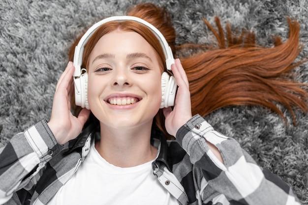 Frau, die draufsicht der musik genießt Kostenlose Fotos
