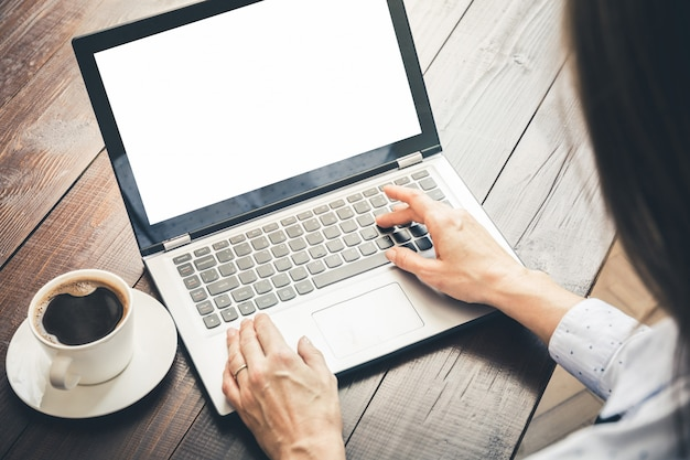Frau, die durch laptop im büro schreibt und sucht. platz auf dem bildschirm für text. Premium Fotos