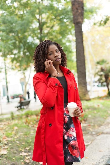 Frau, die durch smartphone und das schauen spricht Kostenlose Fotos