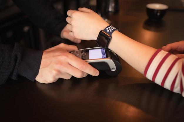 Frau, die durch smartwatch mit nfc-technologie bezahlt Kostenlose Fotos