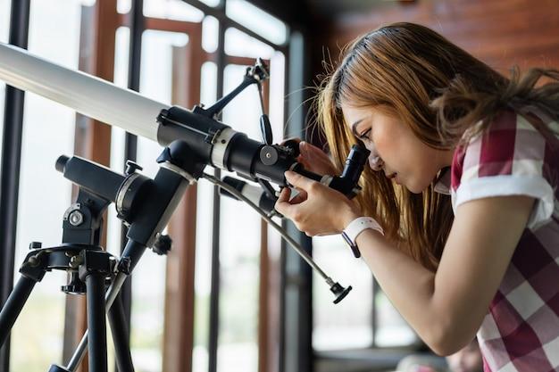 Frau, die durch teleskop schaut Premium Fotos
