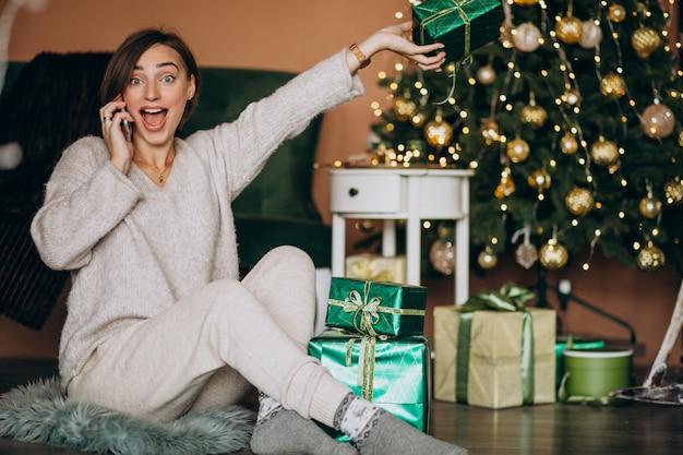 Frau, die durch weihnachtsbaum sitzt und am telefon kauft Kostenlose Fotos