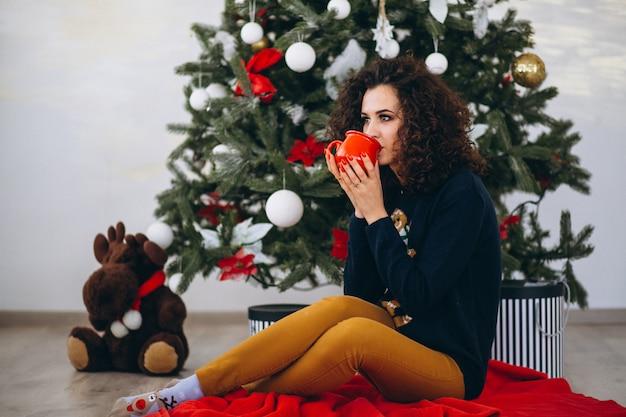 Frau, die durch weihnachtsbaum sitzt und tee trinkt Kostenlose Fotos