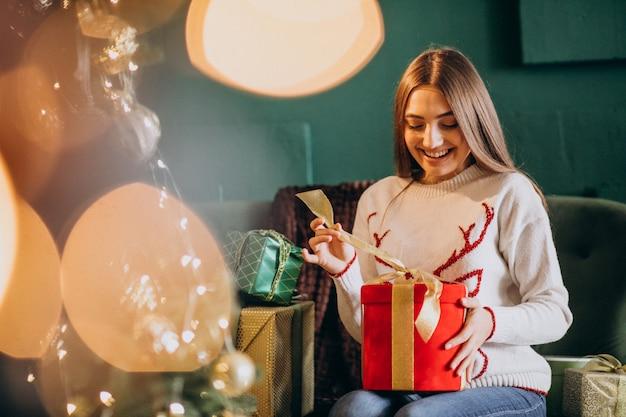 Frau, die durch weihnachtsbaum sitzt und weihnachtsgeschenk auspackt Kostenlose Fotos