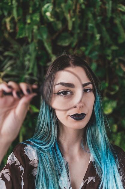 Frau, die ein auge durch ein vergrößerungsglas zeigt Kostenlose Fotos