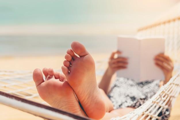 Frau, die ein buch auf hängemattenstrand in den freizeitsommerferien liest Premium Fotos