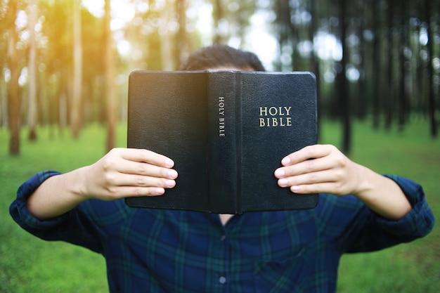 Frau, die ein buch, die bibel, natur hält. Premium Fotos