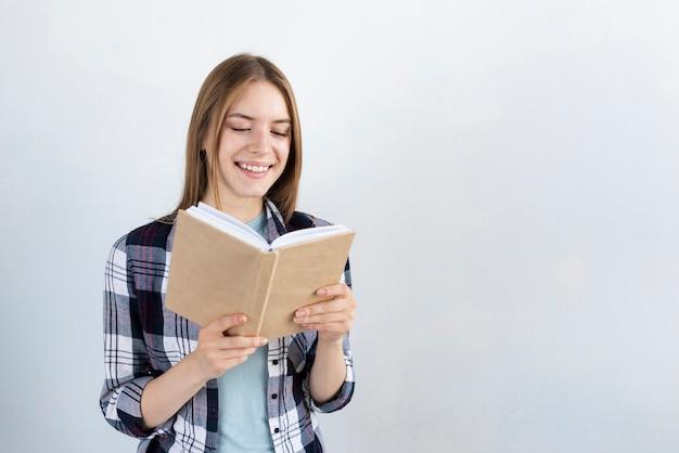 Frau, die ein buch mit exemplarplatz liest Kostenlose Fotos