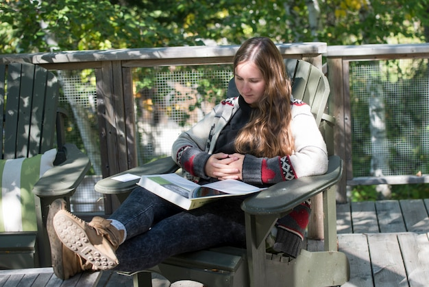Frau, die ein buch, see des holzes, ontario, kanada liest Premium Fotos