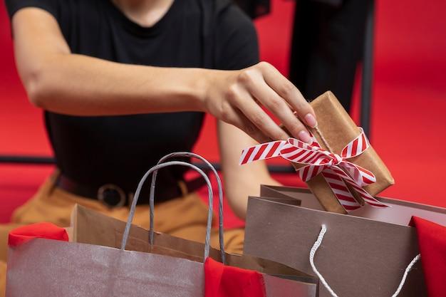 Frau, die ein eingewickeltes geschenk in eine einkaufstaschennahaufnahme einsetzt Kostenlose Fotos