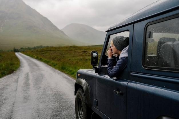 Frau, die ein foto aus dem autofenster macht Kostenlose Fotos