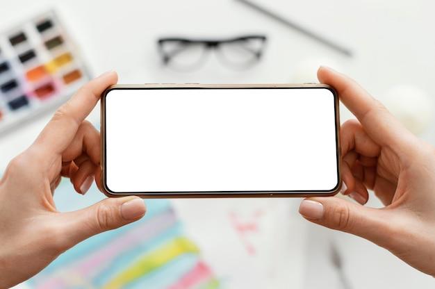 Frau, die ein foto ihrer kunst mit ihrem telefon macht Kostenlose Fotos