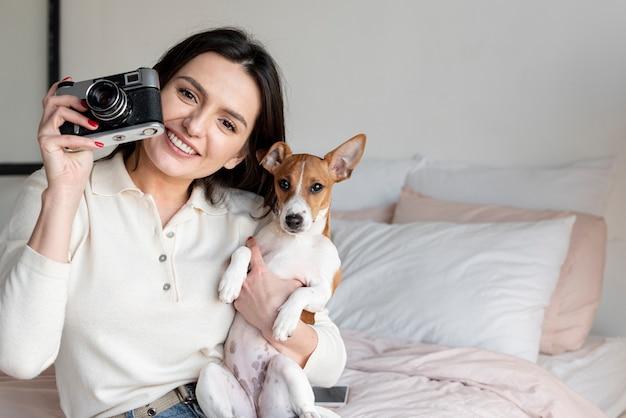 Frau, die ein foto macht, während sie hund hält Kostenlose Fotos