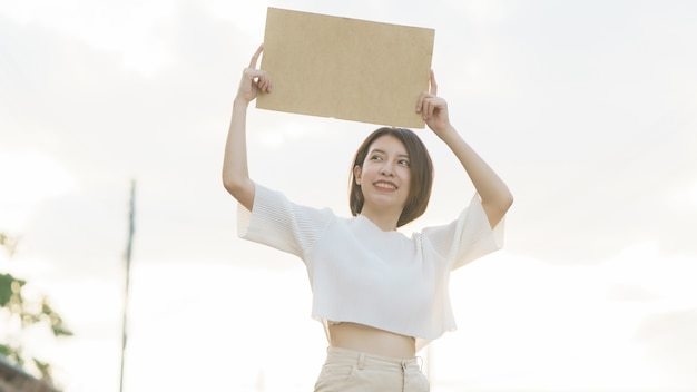Frau, die ein leeres banner hält, um den text auf protest zu setzen. Premium Fotos