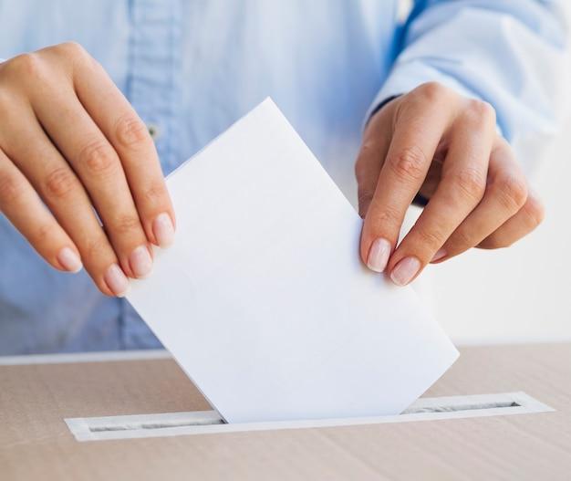 Frau, die ein leeres stimmzettelmodell hält Kostenlose Fotos