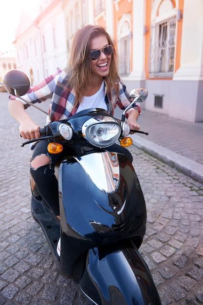 Frau, die ein motorrad in der stadt reitet Kostenlose Fotos